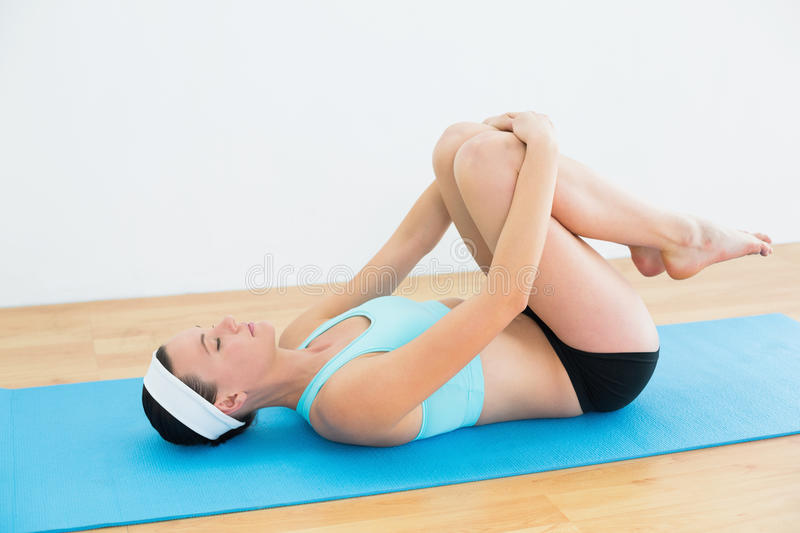 Download Woman In Supine Wind Release Posture On Yoga Mat Stock Photo - Image: 35024780
