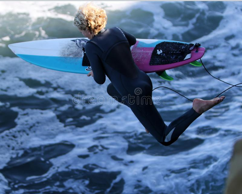 Woman With Surfboard Jumping to Body of Water royalty free stock images