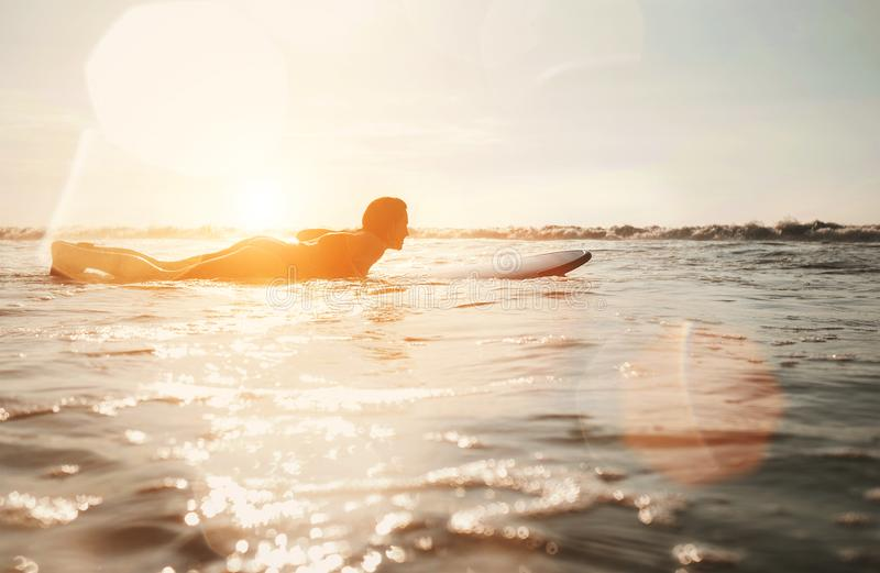 Woman surfer floating on the long surfboard towards line up royalty free stock images