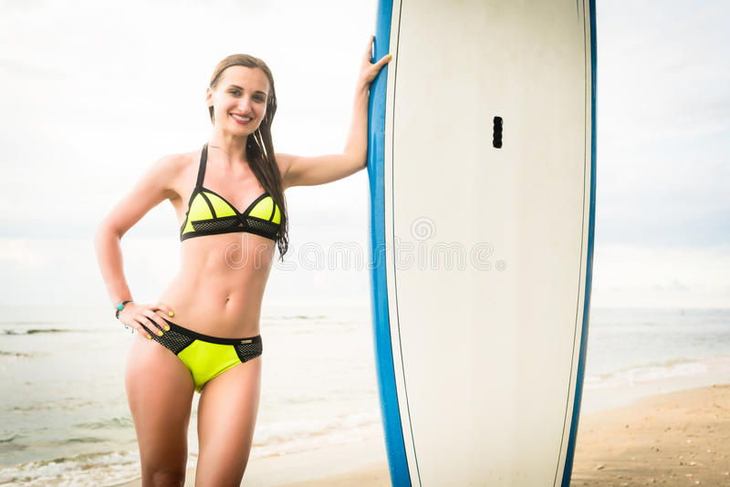 Woman Surfer wearing bikini with Surfboard at beach royalty free stock photography