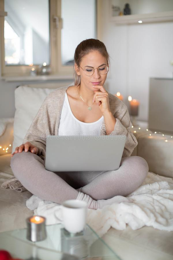 Woman  surfing the net. Beautiful happy woman with blond hair surfing the net/homeoffice royalty free stock photography