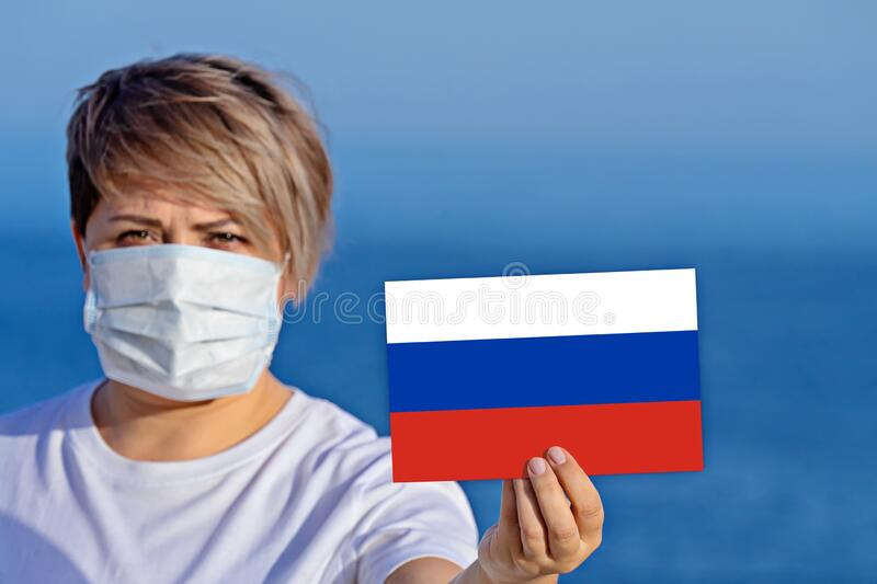 Woman in surgical face mask holds Russian flag confirmed infected people stock photo