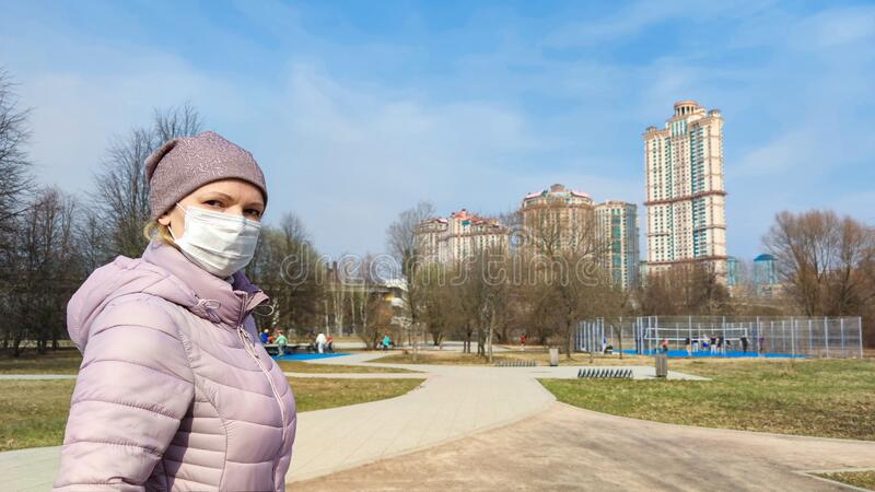 Woman with surgical mask on face in city park during COVID-19 coronavirus pandemic royalty free stock images