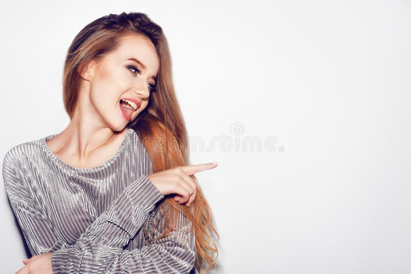 Woman surprise showing product .Beautiful girl with long hair pointing to the side . Make-up. Expressive facial expressions. royalty free stock photos