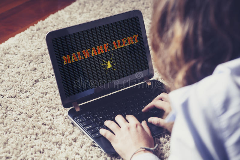 Woman surprised by malware alert while using a laptop computer. royalty free stock images