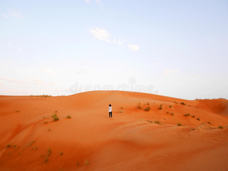 Woman surrounded by large sand dunes of Wahiba desert, Oman stock photos