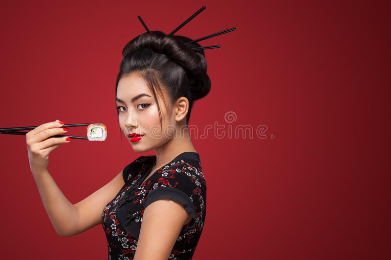 Asian woman eating sushi and rolls on a red background. 8 - Eight March, Black Friday, Setsubun Japanese Festival, sushi royalty free stock photos