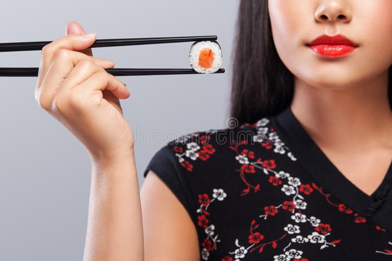 Closeup portrait of asian woman in japanese kimano with sushi and rolls on a gray background. Copy space. stock photography