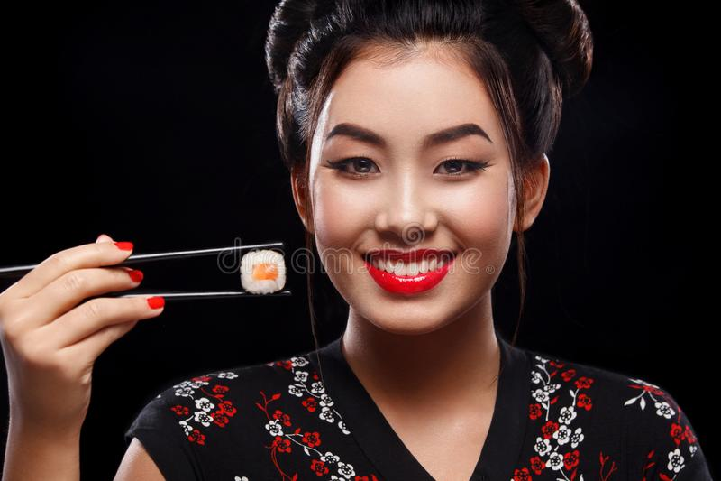 Happy and smiling Asian woman eating sushi and rolls on a black background. royalty free stock photos