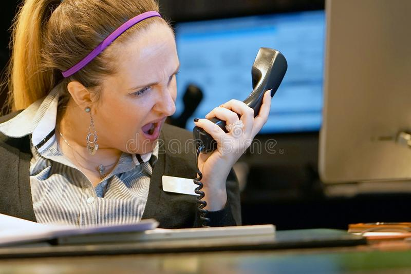 Woman swears with the client by phone stock photos