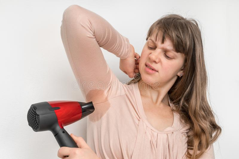 Woman is drying her sweating armpit with hair dryer stock photography