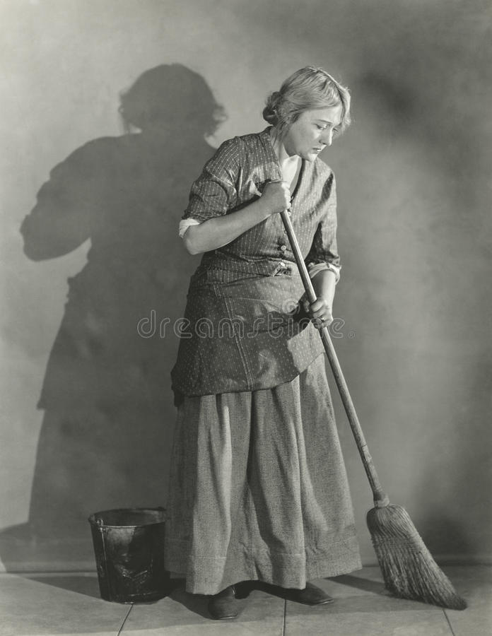 Woman sweeping floor royalty free stock photos
