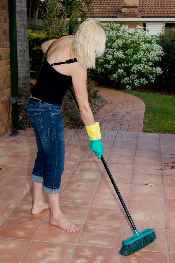 Woman sweeping tiled floor royalty free stock images