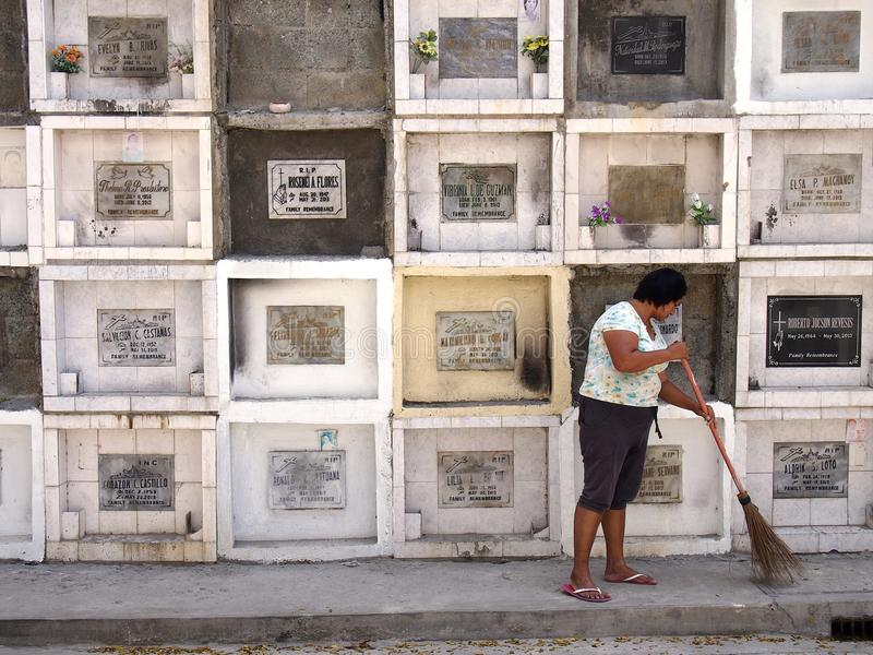 A woman sweeps in front of columns of graves in a cemetery in Antipolo City, Philippines. ANTIPOLO CITY, PHILIPPINES - MARCH 18, 2016: A woman sweeps in front of royalty free stock image