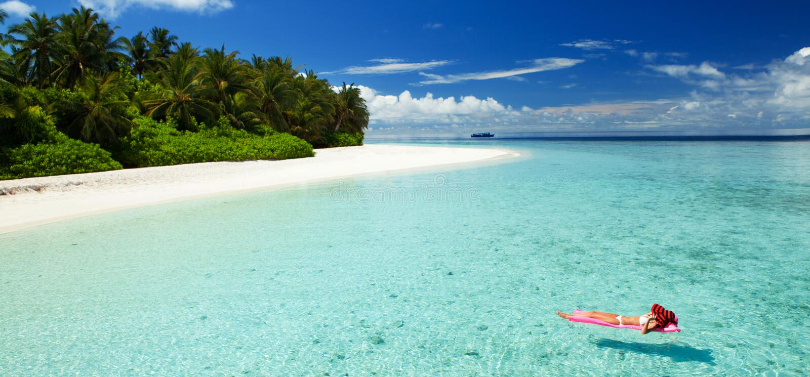 Woman swim and relax in the sea. Happy island lifestyle. White sand, crystal-blue sea of tropical beach. Vacation at Paradise. stock images