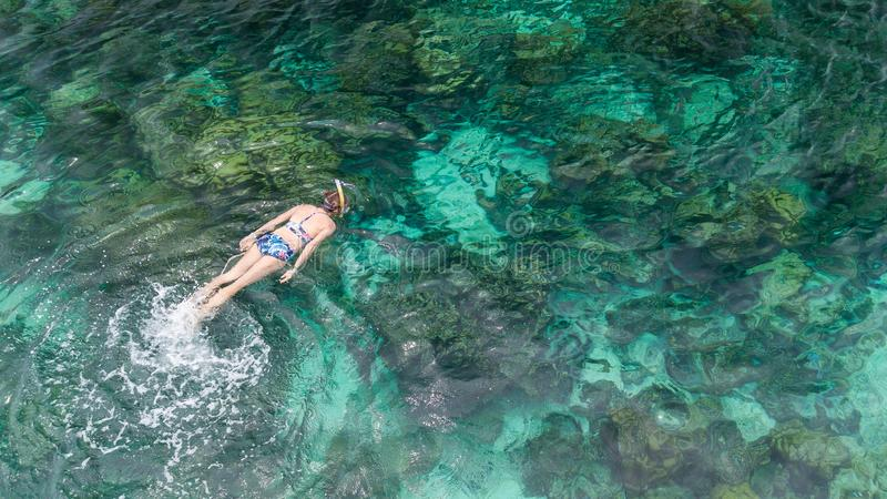 Woman swimming in blue sea. Snorkeling girl in full-face snorkel stock photos