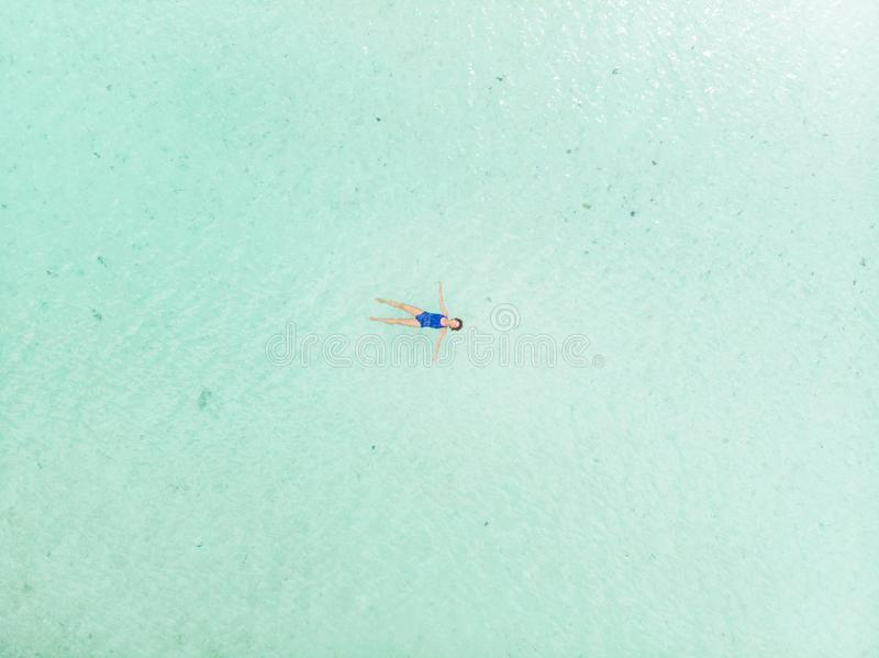 Woman swimming in caribbean sea turquoise transparent water. Aerial top down view, minimal composition. Exotic vacation wellbeing royalty free stock photo