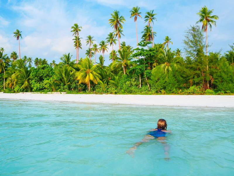 Woman swimming in caribbean sea turquoise transparent water. Tropical beach in the Kei Islands Moluccas, summer tourist royalty free stock images
