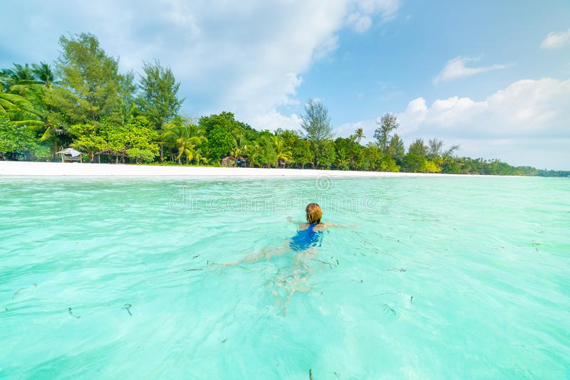 Woman swimming in caribbean sea turquoise transparent water. Tropical beach in the Kei Islands Moluccas, summer tourist stock images