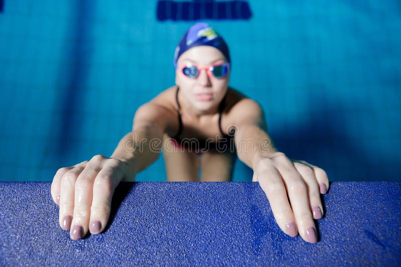 Woman swimming with swimming hat in swimming pool royalty free stock images
