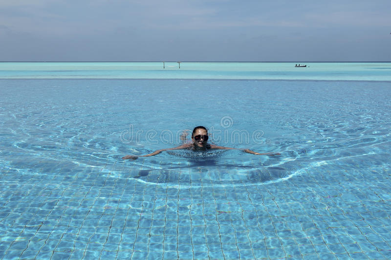 Woman swimming in infinity pool in Maldives royalty free stock photos