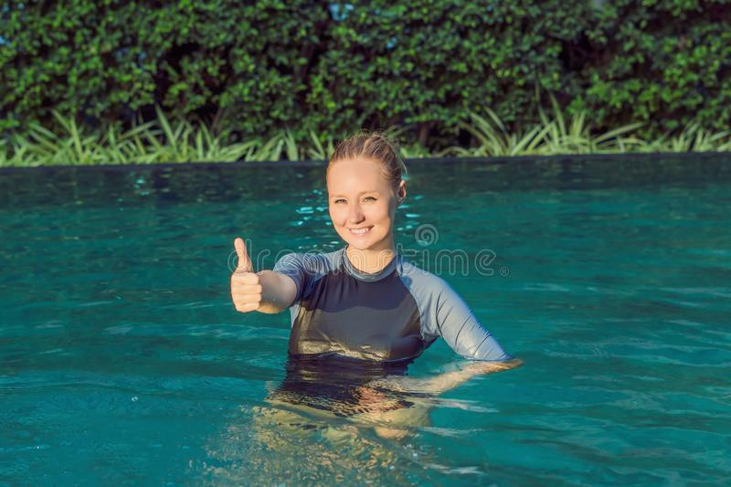 Woman swimming instructor for children is teaching a happy boy to swim in the pool stock photography