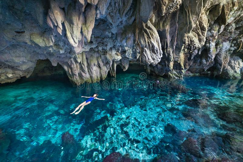 Woman swimming in natural lake inside cave. Colorful reflection, turquoise transparent water, summer adventures. Tourist royalty free stock images