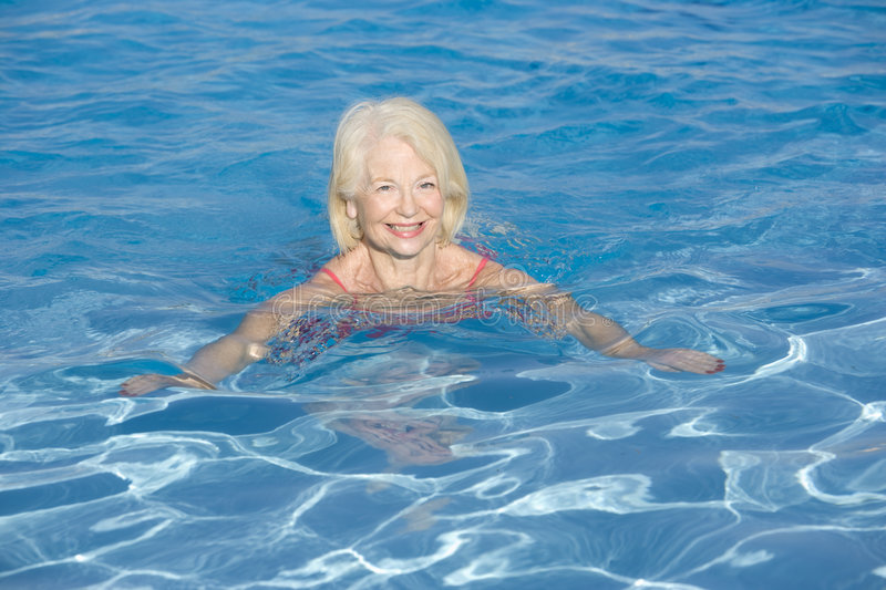 Woman swimming in outdoor pool smiling royalty free stock image