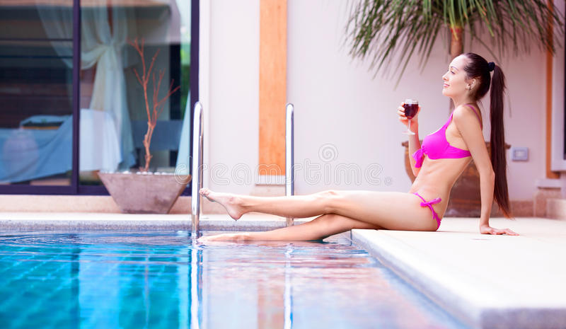 Woman by the swimming pool stock image