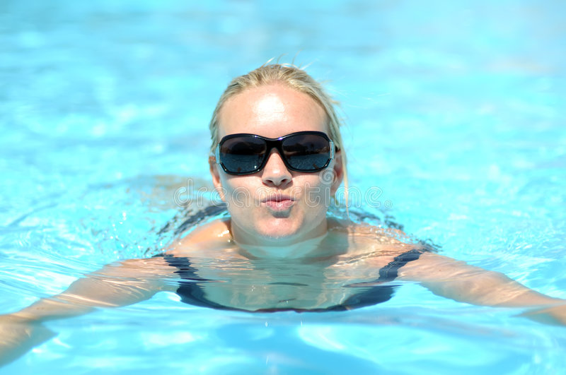 Woman swimming in pool stock image