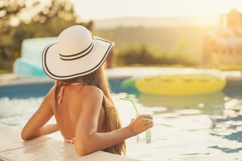 Woman at a swimming pool. Attractive young women wearing bikini and a hat, standing in the swimming pool, enjoying beautiful summer sunset, looking away from the stock photos
