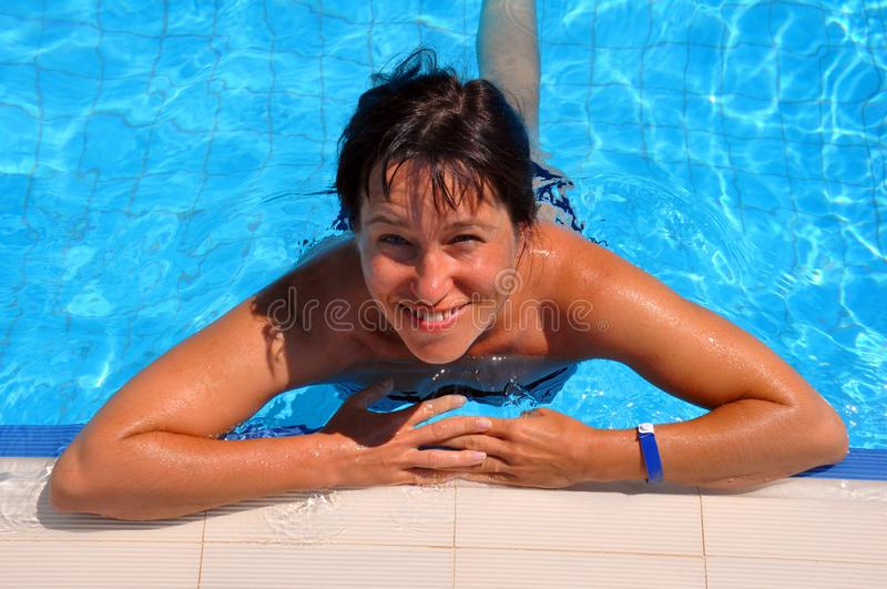 A woman in a swimming pool hangs on the side. Happy smiling royalty free stock images