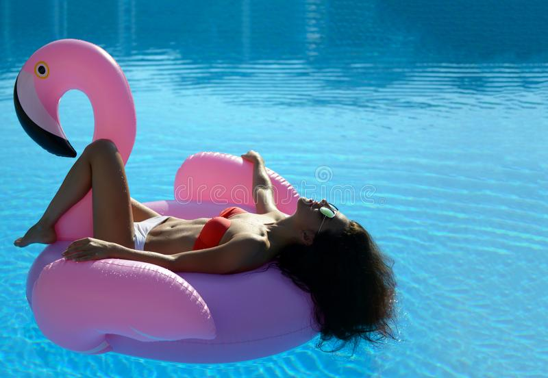 Woman in a swimming pool leisure on a giant inflatable giant pink flamingo float mattress in red bikini. Young pretty woman relaxing in a swimming pool leisure royalty free stock images