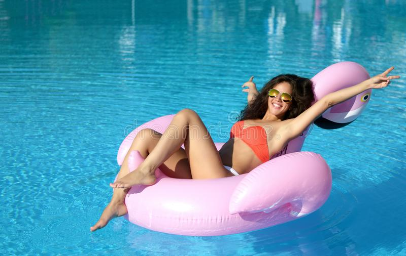 Woman in a swimming pool leisure on a giant inflatable giant pink flamingo float mattress in red bikini. Young pretty woman relaxing in a swimming pool leisure stock photo