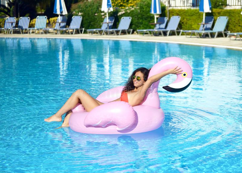 Woman in a swimming pool leisure on a giant inflatable giant pink flamingo float mattress in red bikini. Young pretty woman relaxing in a swimming pool leisure stock image