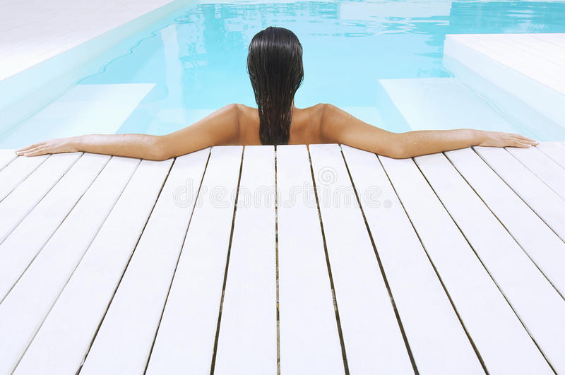 Woman In Swimming Pool Resting On Poolside stock photography