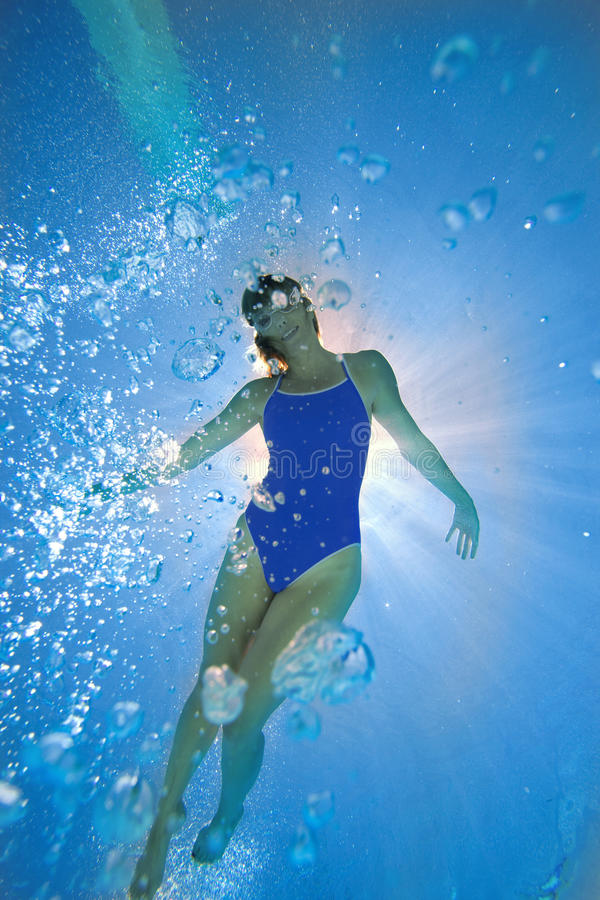 Woman in swimming pool, underwater view (lens flare) royalty free stock images