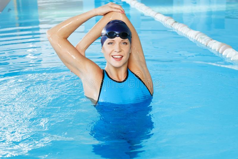 Woman in swimming pool. Young woman wearing blue swimming suit and cap in swimming pool royalty free stock image