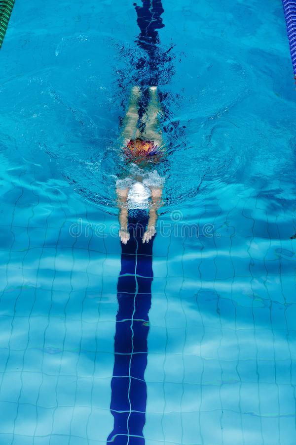 Woman swimming with swimming hat in swimming pool stock photos