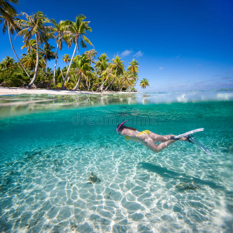 Woman swimming underwater. In clear tropical waters in front of exotic island