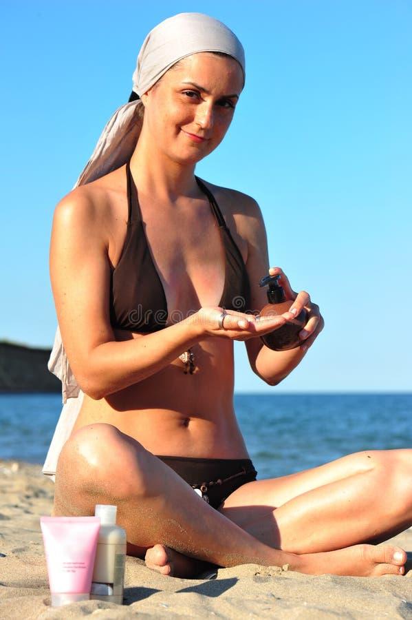 Woman in swimsuit applying sun lotion