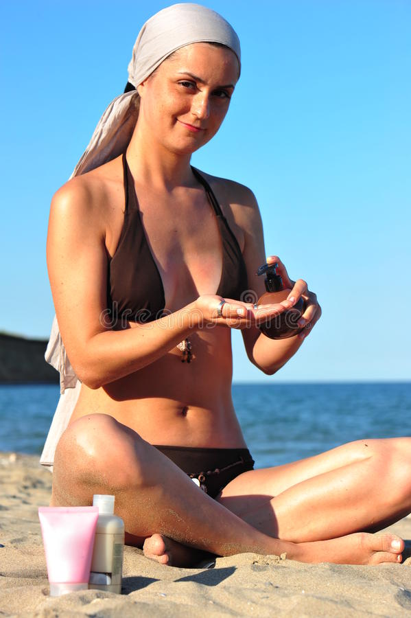 Woman In Swimsuit Applying Sun Lotion Stock Photos