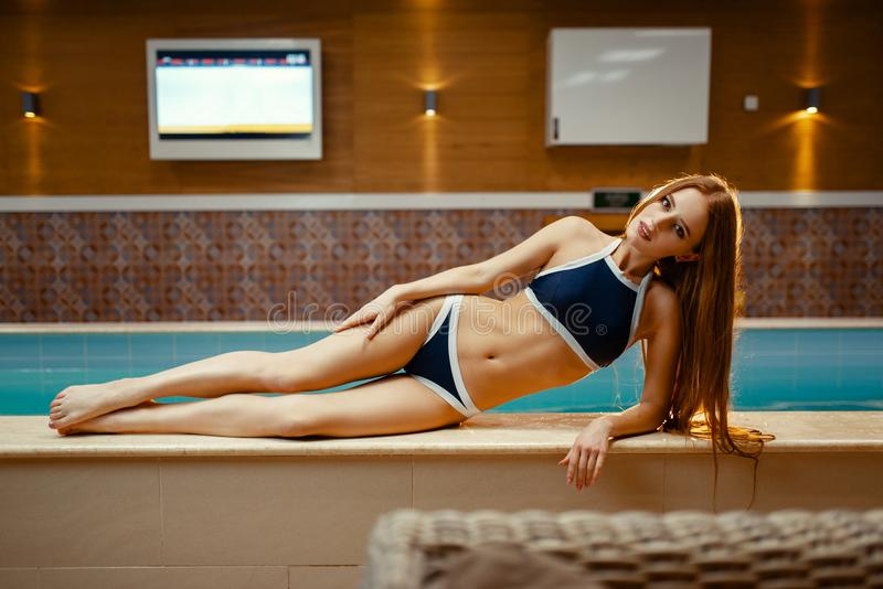 Woman in swimsuit lying at the pool indoors royalty free stock photos