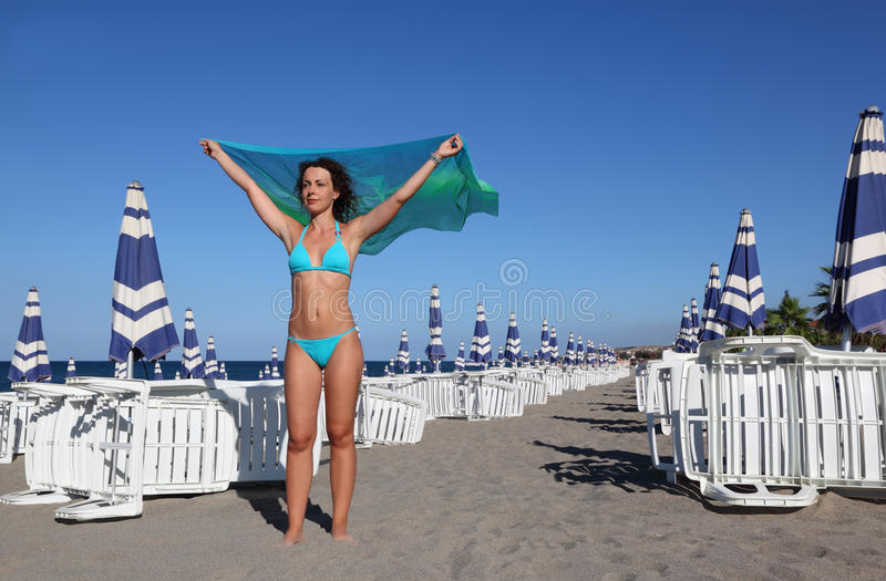Woman in swimsuit and pair stands on beach stock image