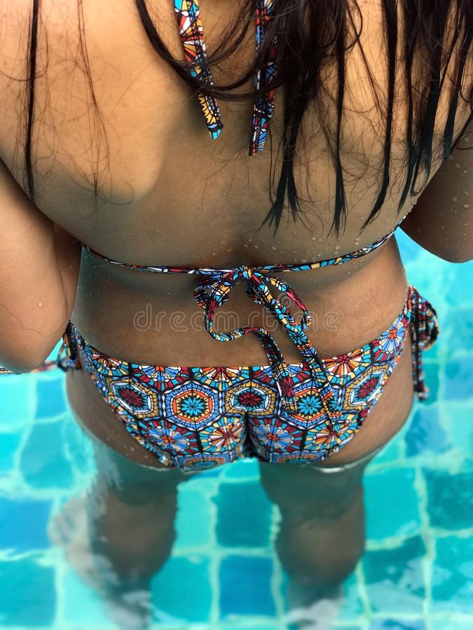 A  woman in swimsuit standing in a blue pool, rear view. stock photos