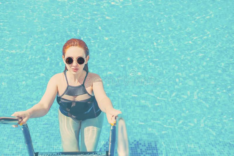 A woman getting out of the blue water in the pool. Woman with swimsuit swimming on a blue water pool. Toned. Pretty female body coming out of the pool stock photos