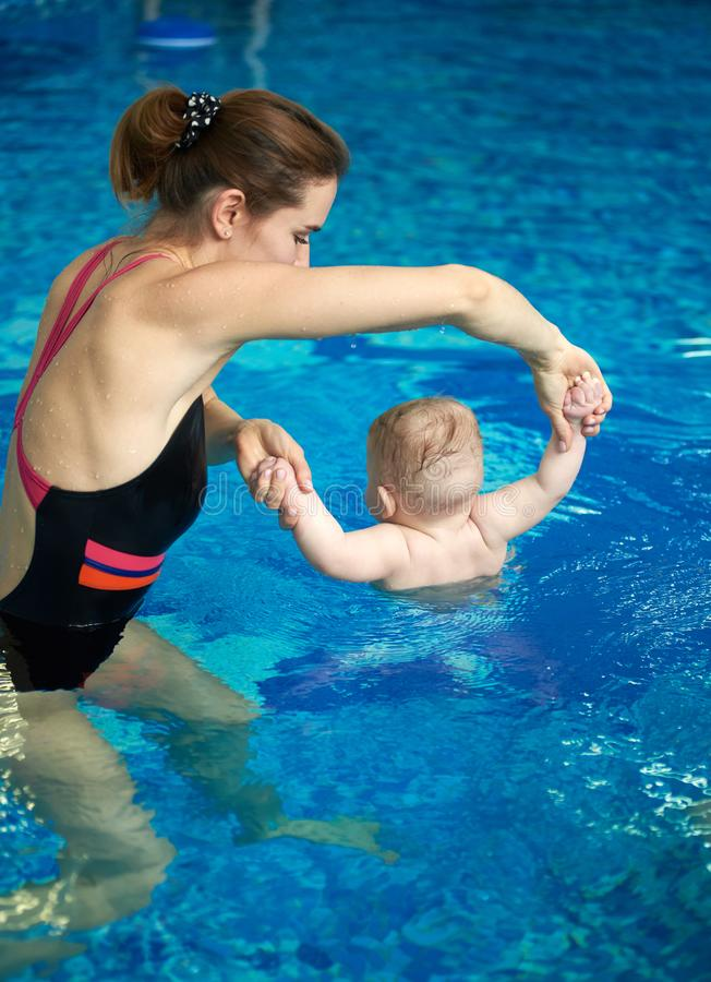 Woman and baby doing exercises floating in upright position in shallow pool. Hardening and disease prevention. Back view stock images