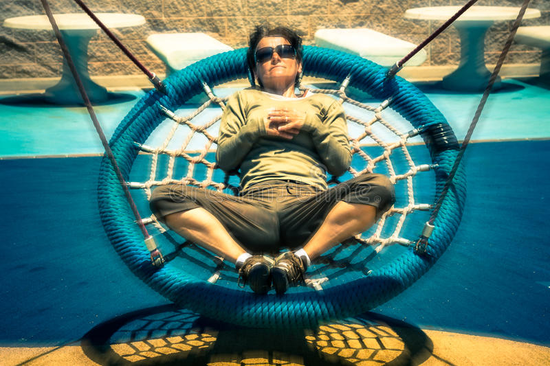 Woman on swing. Middle aged woman relaxing on swing outdoors. Colorful toned photo with motion blur effect
