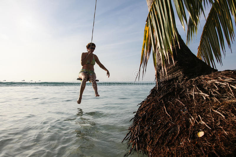 Woman on a swing at the beach. royalty free stock image