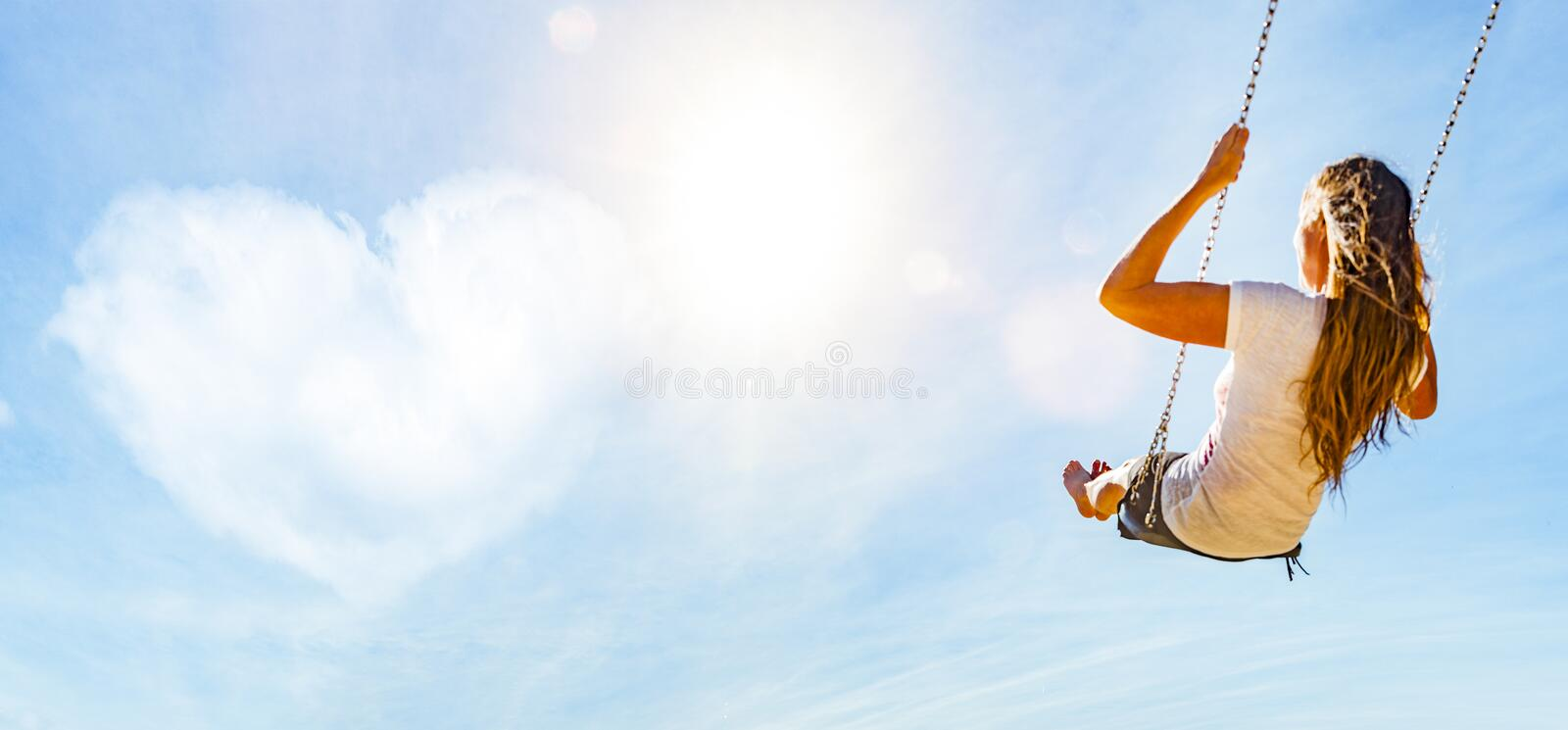 Woman on a swing with blue sky and heart-shaped cloud stock photography